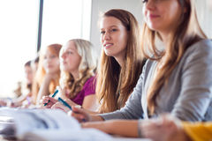 Students in classroom - young pretty female college student Stock Image