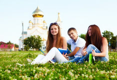 Students in a clearing in  background of church Royalty Free Stock Photo