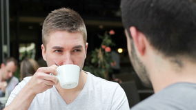 Students in the coffee shop. Two young handsome caucasian men relaxing outside, drinking coffee stock footage