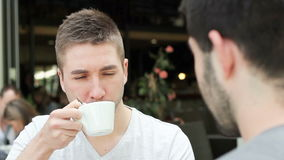 Students in the coffee shop. Two young handsome caucasian men relaxing outside, drinking coffee stock video footage