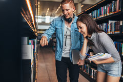 Students at college library looking for books. Image of happy young men and women standing by book shelf in library and looking for books. Students at college Stock Photography
