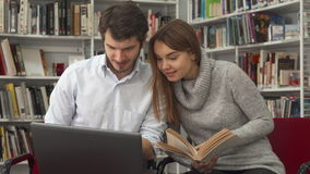 Students compare information in the book and on the laptop at the library stock footage