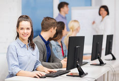 Students with computer monitor at school. Education, techology and internet concept - group of smiling students with computer monitor looking at teacher at Stock Photos