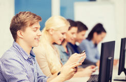 Students with computer monitor and smartphones Stock Image