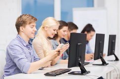 Students with computer monitor and smartphones Royalty Free Stock Image