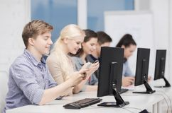 Students with computer monitor and smartphones Royalty Free Stock Images