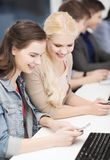 Students with computer monitor and smartphones Royalty Free Stock Photo