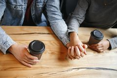 Students couple having a romatic lunch indoors closeness. Young boyfriend and girlfriend diverse couple students having a romantic coffee-break drinking hot Stock Photography