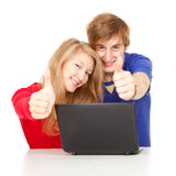 Students couple with thumbs up using laptop. Young students couple with thumbs up using laptop Stock Photos