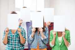 Students covering faces with blank papers. Education concept - group of students covering faces with blank papers Royalty Free Stock Photo