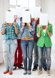 Students covering faces with blank papers. Education concept - group of students covering faces with blank papers Royalty Free Stock Image