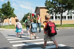 Students crossing street. A view of elementary students crossing the street on their way to school under the watchful eye of a crossing guard Royalty Free Stock Photo