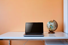 Students desk with globe and laptop. With place for text on the wall Stock Images