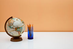 Students desk with globe and pencils Stock Photo