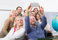 Students of different age doing group selfie on smartphone Stock Photo