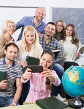 Students of different age doing group selfie on smartphone Royalty Free Stock Image