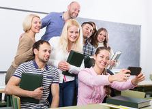 Students of different age doing group selfie on smartphone Royalty Free Stock Images