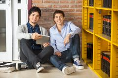 Students With Digital Tablet Sitting In University. Portrait of male students with digital tablet sitting in university library Royalty Free Stock Photography