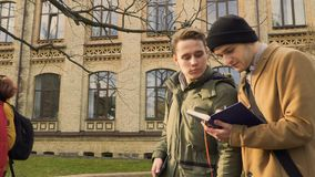 Students discuss future lecture walking in park near university stock video footage