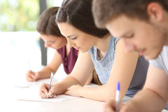 Students doing an exam in a classroom. Close up of three concentrated students doing an exam in a classroom Stock Photography