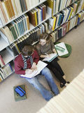 Students Doing Homework On Floor In Library Royalty Free Stock Image