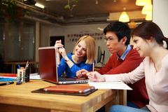 Students doing homework with laptop together. Happy students doing homework with laptop together Stock Photos