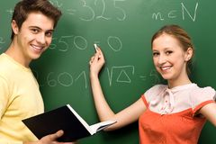 Students Doing Math on Chalkboard Royalty Free Stock Images