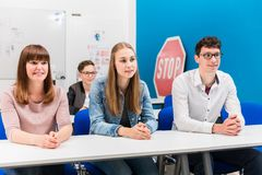 Students in driving lessons listening attentively. Sitting on benches stock images