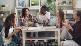 Students eating toasting and drinking at party in house having fun together. Female and male students are eating toasting and drinking at enjoyable party in stock video footage