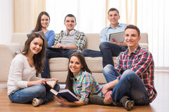 Students. Education and people concept. Group of students with books, and laptop are looking at the camera while resting in room Royalty Free Stock Photography