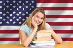 Students with elbows on the books against American flag background. Digital composite of students against American flag Stock Photos