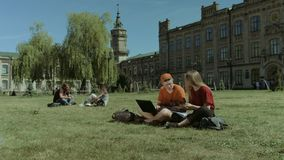 Students with electronic devices studying on lawn. Positive college students studying with smart technology devices and talking while sitting cross-legged on stock video footage
