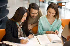 Students engrossed in their studies at library. Young people sitting at table working on school project in library.  University students taking reference from Royalty Free Stock Images