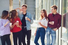 Students enjoying cup of coffee to go on street. stock photos