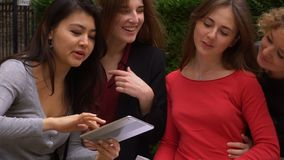 Students enjoying with tablet near university building and learning English with papers in slow motion. Female students translating words by tablets and stock video footage