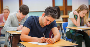 Students in an exam. Students sitting in an exam hall doing an exam in university stock photo