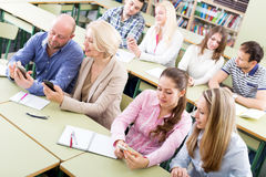 Students of at extension courses. Smiling students of different age at extension courses.Focus on the women in pink shirt Royalty Free Stock Image
