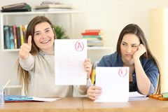 Students with failed and approved exams. Front view portrait of two students showing failed and approved exams at home royalty free stock photography