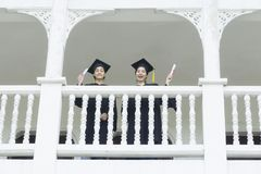 Students in feeling happy with graduation gowns stand at corrido. The students in feeling happy with graduation gowns stand at corridor building Stock Photos