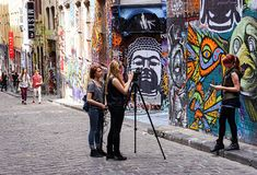 Students filming interview in front of graffiti art