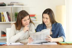 Students finding suspicious news in a newspaper. Front view portrait of two students finding suspicious news in a newspaper at home stock photos