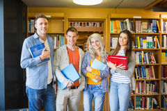 Students with folders against bookshelf in library Royalty Free Stock Images
