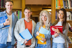 Students with folders standing against bookshelf in library Royalty Free Stock Photography