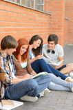 Students friends sitting on ground outside campus Stock Photo