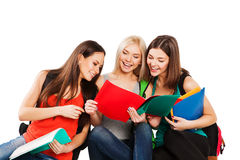 Students, friends sitting together on a white. Students girl sitting together on a white background Royalty Free Stock Photography