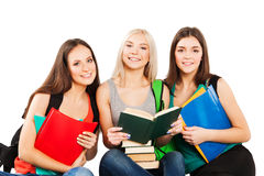 Students, friends sitting together on a white. Smiling students sitting together on a white background Royalty Free Stock Photo