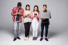 Students friends using gadgets isolated on white. Students friends using smartphones near by isolated on white Royalty Free Stock Photo