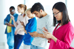 Students with gadgets. Group of contemporary multi-ethnic students using gadgets Royalty Free Stock Images