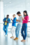 Students with gadgets. Modern students with gadgets standing in row Stock Images