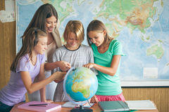 Students in a Geography Lesson. Three students examining a globe with their teacher in a geography lesson royalty free stock photography